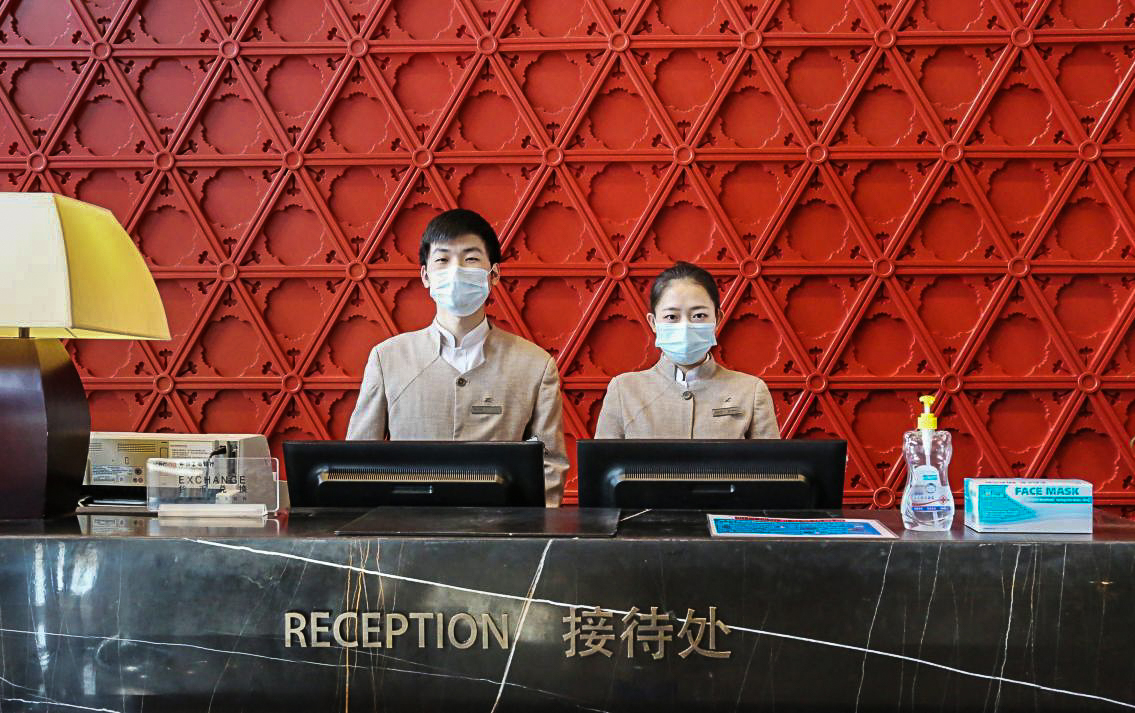 Front office at luxury hotel with staff wearing masks